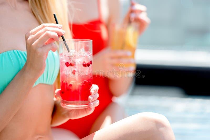 tir cultivé des femmes dans le bikini et le maillot de bain tenant des verres image stock