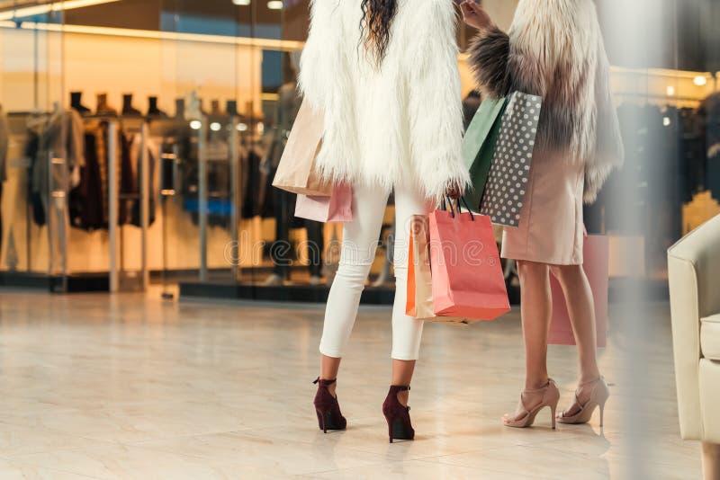 tir cultivé des filles dans des manteaux de fourrure tenant des sacs en papier tout en faisant des emplettes ensemble dans le mai images stock