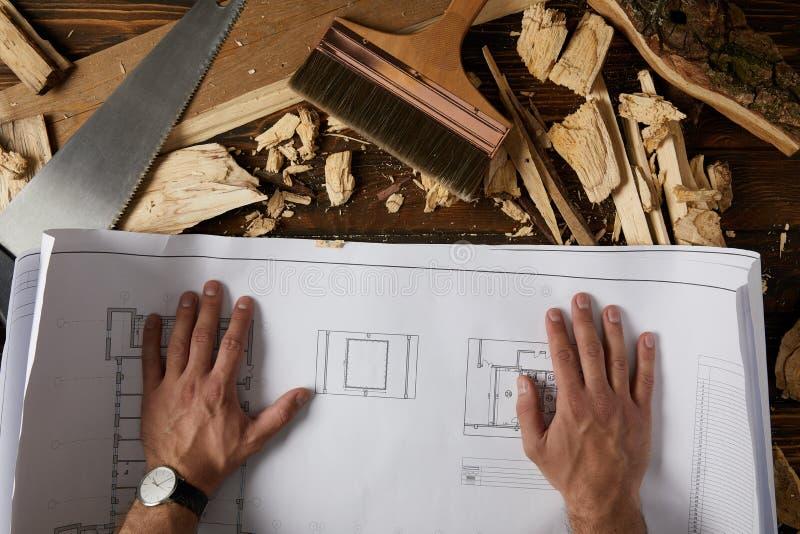 tir cultivé des mains d'architecte sur le modèle à la table avec le pinceau, la scie à main et les puces en bois sur la table photo libre de droits