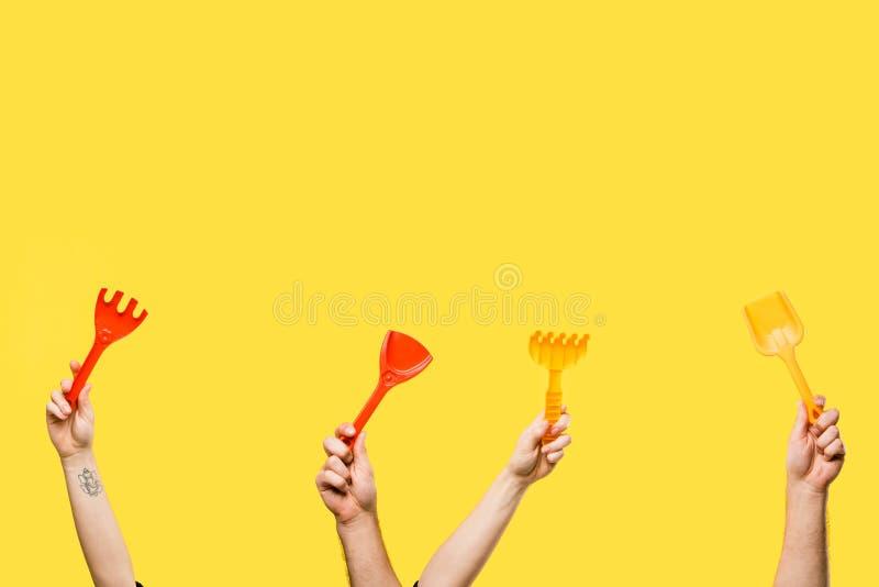 tir cultivé des mains masculines et femelles tenant les pelles rouges et jaunes et les râteaux en plastique d'isolement photo stock