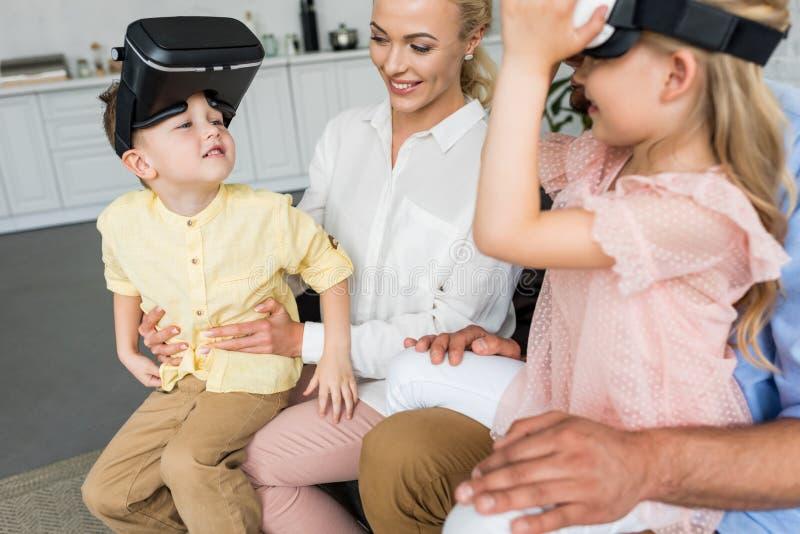 tir cultivé des parents jouant avec des enfants utilisant des casques de réalité virtuelle image libre de droits