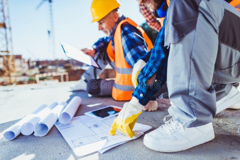 Tir cultivé des travailleurs de la construction dans l'uniforme se reposant sur le béton au chantier de construction, examinant photos stock