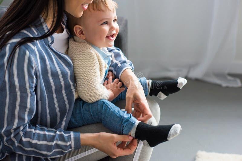 tir cultivé du habillage de mère gai petit bébé sur le sofa images stock