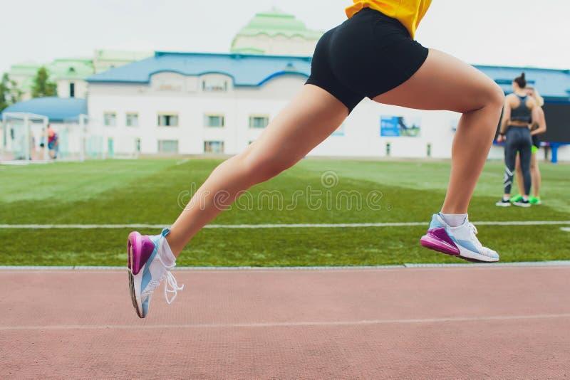 Tir cultivé du jeune athlète féminin lançant outre de la ligne de début dans une course Le coureur femelle a commencé le sprint à images stock