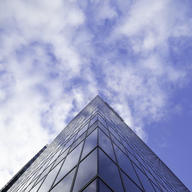 Tir d'angle faible d'un bâtiment en verre grand d'affaires de gratte-ciel avec le ciel nuageux à l'arrière-plan photo libre de droits