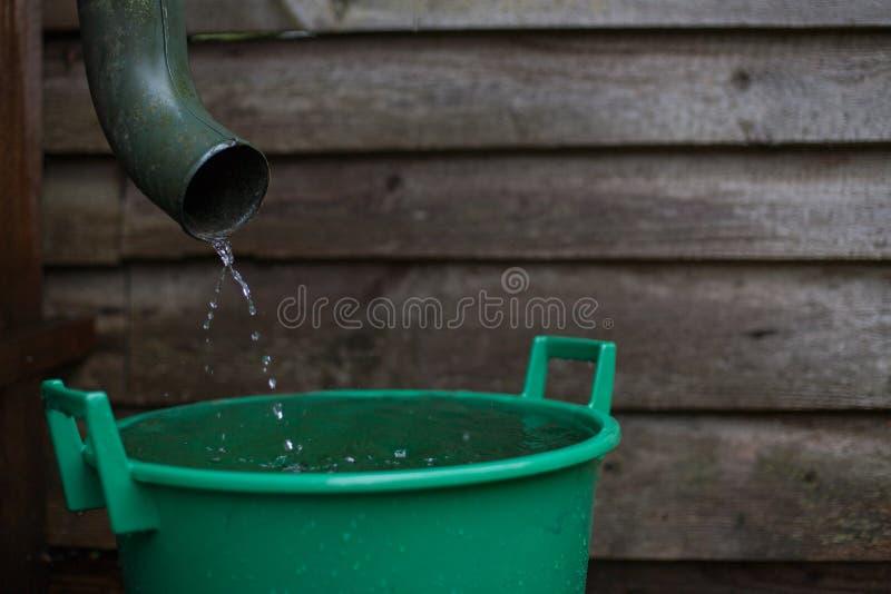 Tir d'eau de pluie d'une gouttière dans une eau rassemblant le réservoir images stock