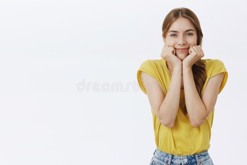 Tir d'intérieur de charmer la femme caucasienne mince avec la tête de penchement de belle peau propre sur des paumes souriant joy image stock