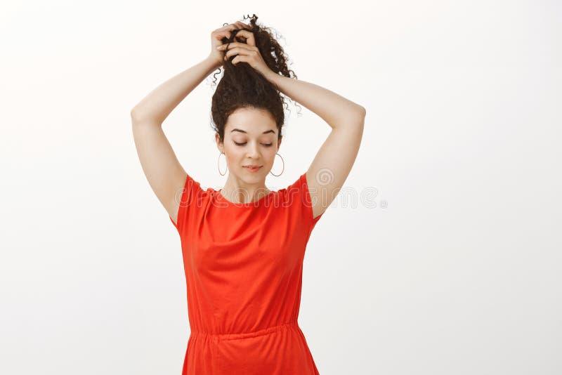 Tir d'intérieur de femelle sûre féminine dans la robe rouge, souriant tendrement et regardant vers le bas tout en peignant les ch images libres de droits