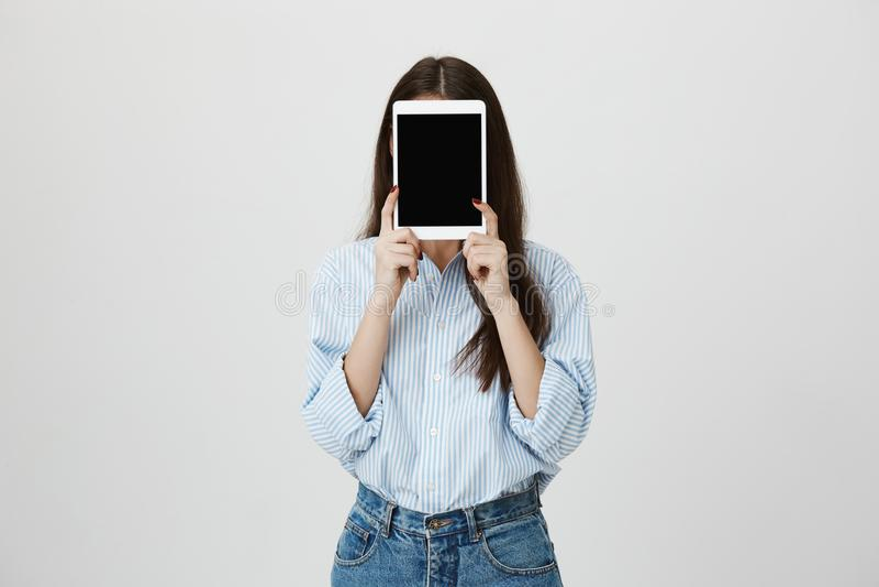 Tir d'intérieur de femme avec de longs cheveux, chemise rayée bleue de port et jeans, couvrant le visage de comprimé blanc, se te photos stock