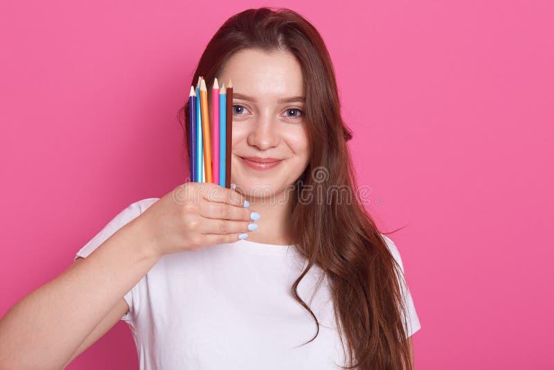 Tir d'intérieur de fille avec de longs cheveux tenant des crayons ou des crayons au-dessus du fond rose, étudiant de sourire avec photographie stock