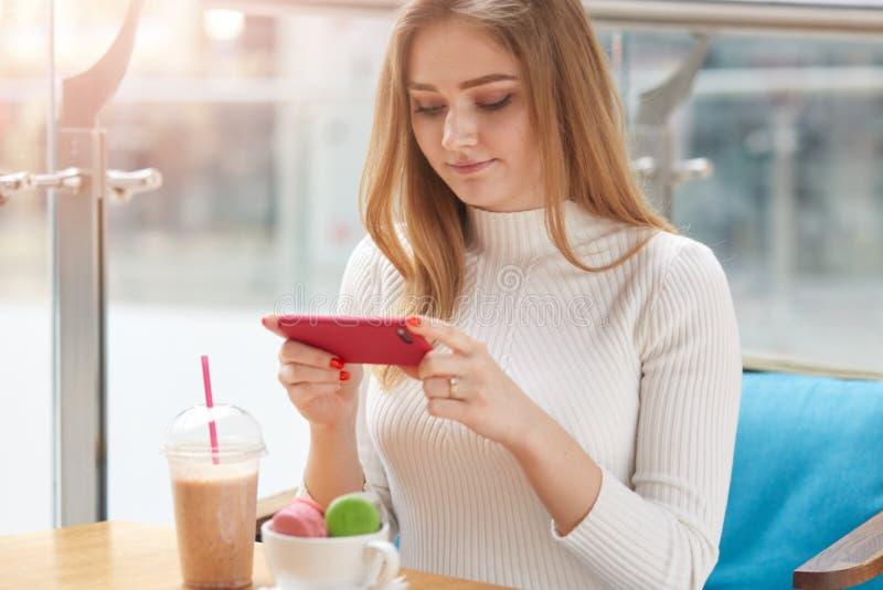 Tir d'intérieur de la jeune séance femelle adorable à la table dans le cafétéria, prenant la photo des macarons dans la tasse, te image stock