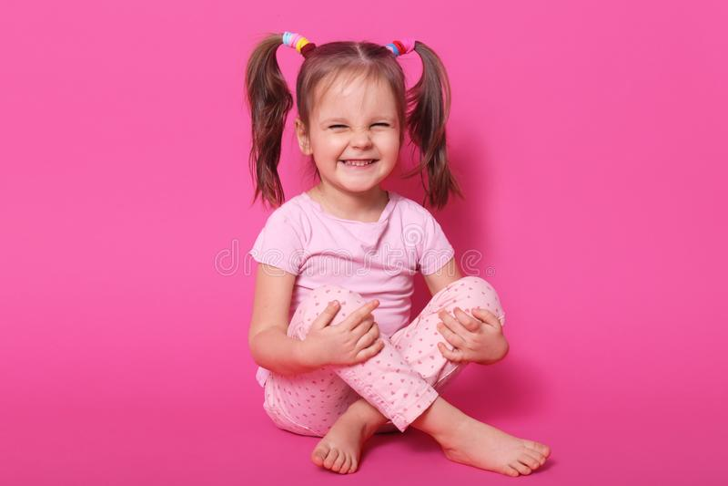 Tir d'intérieur de studio de rire l'enfant positif s'asseyant sur le plancher, pose d'isolement au-dessus du fond rose, T-shirt r photographie stock