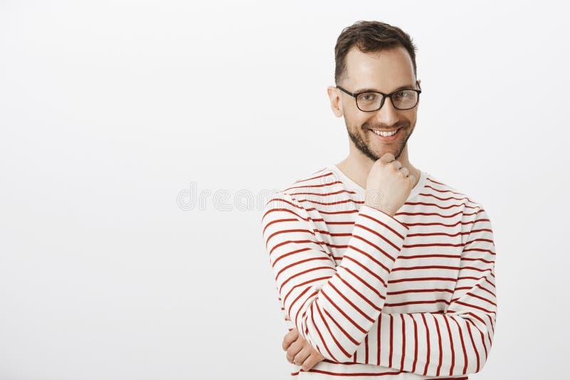 Tir d'intérieur de type gai beau espiègle en verres noirs, souriant avec l'expression intriguée, en ayant intéressant photographie stock