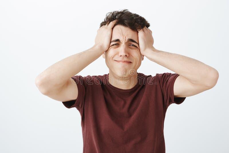 Tir d'intérieur de type sombre désespéré malheureux dans l'équipement occasionnel, tenant des mains sur les cheveux malpropres et images stock