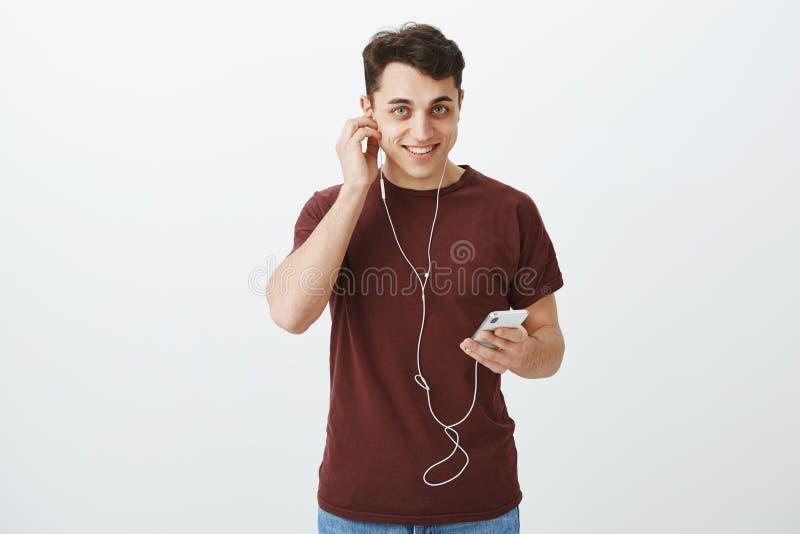 Tir d'intérieur d'homme européen joyeux avec du charme dans le T-shirt rouge, mettant sur des écouteurs et tenant le smartphone,  photo libre de droits