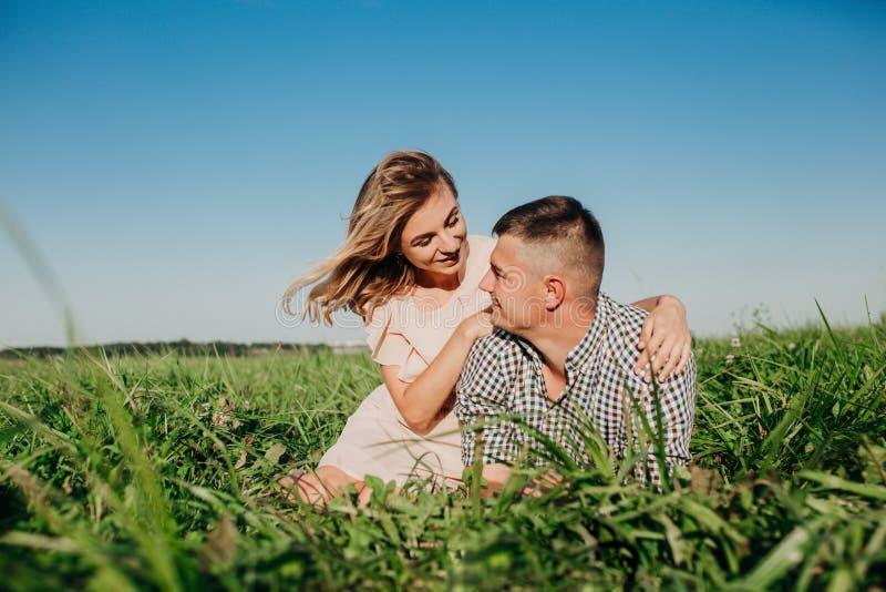 Tir de belle jeune femme se reposant dehors avec son ami Couples dans le pré photo stock