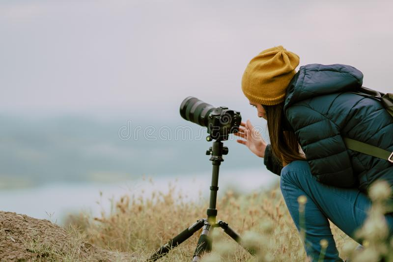Tir de jeune femme avec l'appareil-photo au matin Trépied et appareil-photo mirrorless photographie stock libre de droits