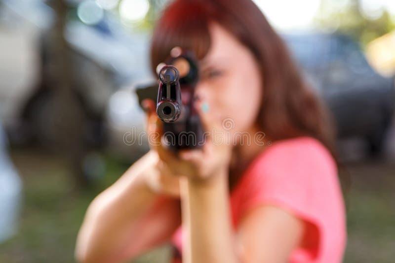 Tir de jeune femme du pistolet pneumatique télescopique, foyer sur des sig avant images libres de droits