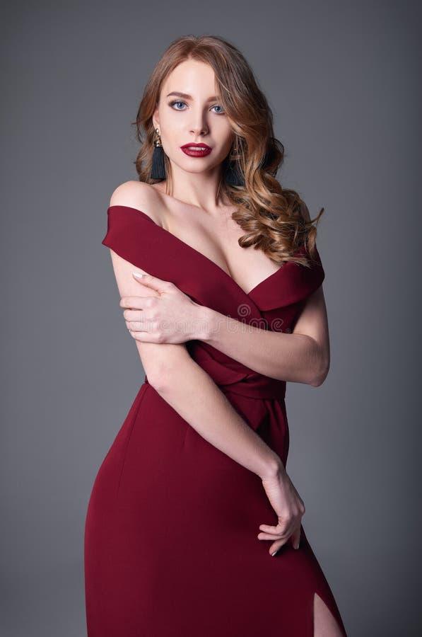 Tir de mode de studio : portrait de belle jeune femme de sourire dans la robe rouge photo stock