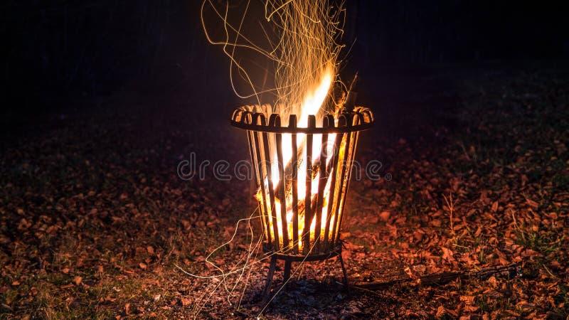 Tir de nuit d'un feu brûlant dans un panier en métal avec des feuilles au sol images stock