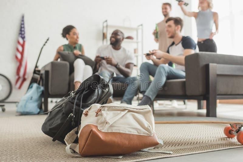 tir de plan rapproché de deux sacs à dos et longboard sur le premier plan et groupe d'amis multi-ethniques avec le jeu de manette photographie stock libre de droits
