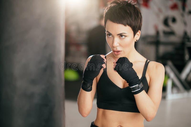 Tir de plan rapproché de femme musculaire apprenant à battre avec des poings à l'intérieur image libre de droits