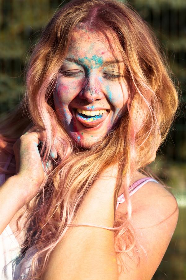 Tir de plan rapproché de jeune femme heureuse couvert de pai coloré de Holi photographie stock
