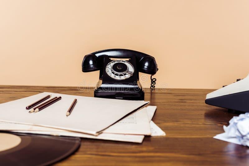 tir de plan rapproché de téléphone rotatoire sur la table en bois avec le disque de machine à écrire et de vinyle photo stock