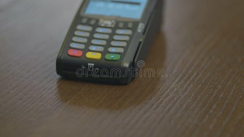 Tir de plan rapproch? du salaire de client au-dessus du carte-lecteur sans fil de commerces Mains humaines adultes de carte banca images libres de droits