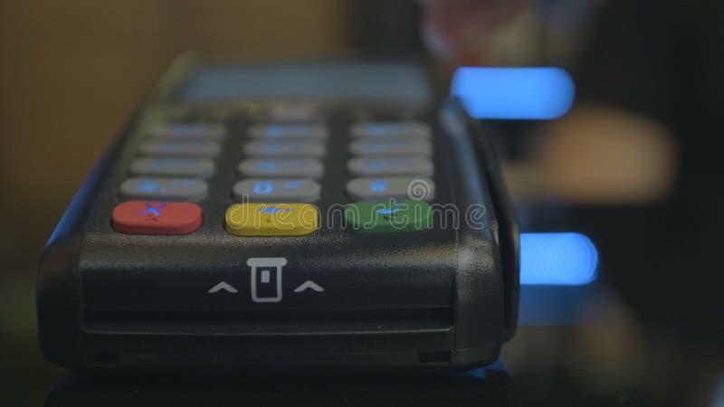 Tir de plan rapproch? du salaire de client au-dessus du carte-lecteur sans fil de commerces Mains humaines adultes de carte banca photo stock