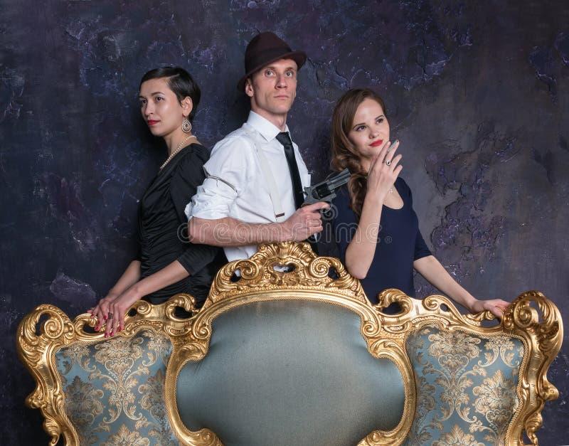 Tir de studio de roman policier Homme et deux femmes Agent 007 Un homme dans un chapeau avec un pistolet et deux femmes dans le n photos stock