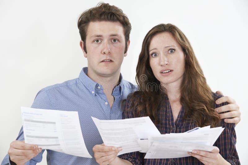 Tir de studio des couples inquiétés regardant des factures images stock