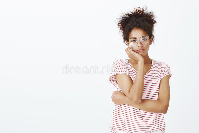 Tir de studio de fille mignonne indifférente ennuyée en T-shirt et verres rayés, regardant avec l'expression négligente photo stock
