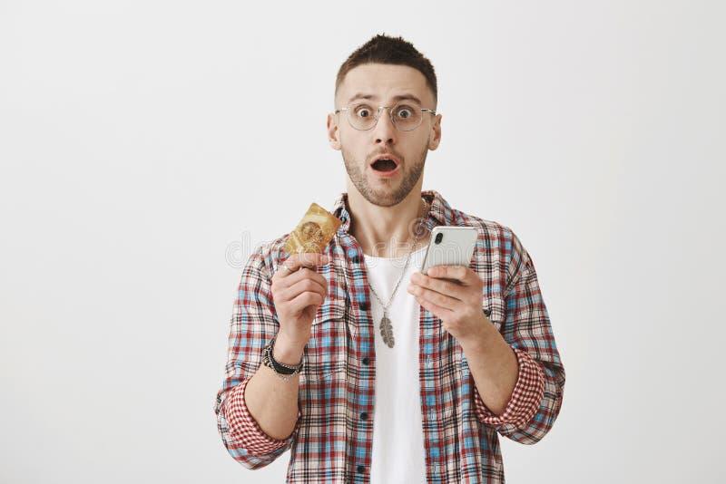 Tir de studio jeune de l'homme européen choqué et terrifié tenant la carte de crédit et le smartphone, se tenant avec la bouche o image stock