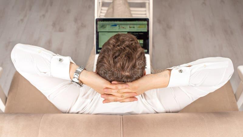 Tir de studio de l'homme se reposant avec ses mains derrière sa tête travaillant à sa vue d'ordinateur portable, supérieure et ar photos libres de droits