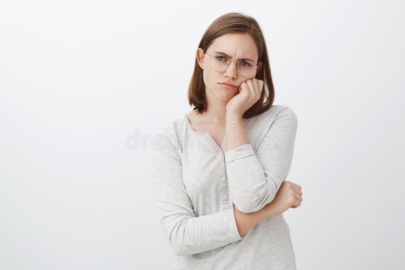 Tir de studio de la jeune femme mignonne contrariée et malheureuse seule en verres avec les cheveux bruns courts fronçant les sou photo libre de droits