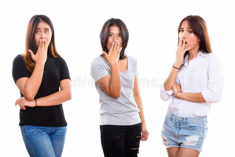 Tir de studio de trois jeunes amis asiatiques de femme semblant choqués photo stock