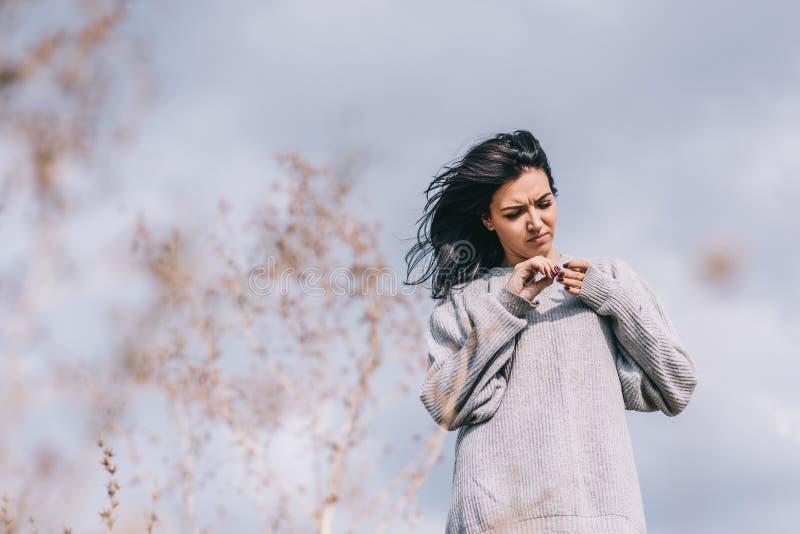 Tir de voyageuse caucasienne de jeune femme de brune attrayante avec les cheveux venteux, posant contre le ciel obscurci Femelle  images libres de droits