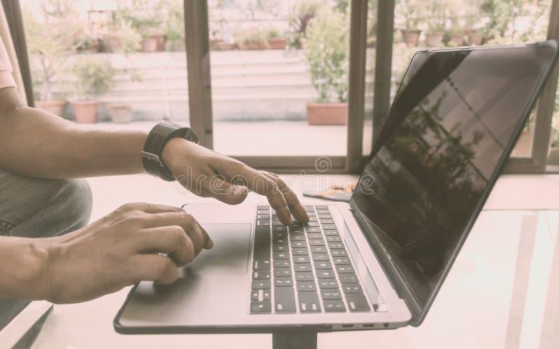 Tir de vue de côté des mains d'un homme occupé d'affaires travaillant dans l'ordinateur portable de carnet faisant le projet sur  photo libre de droits