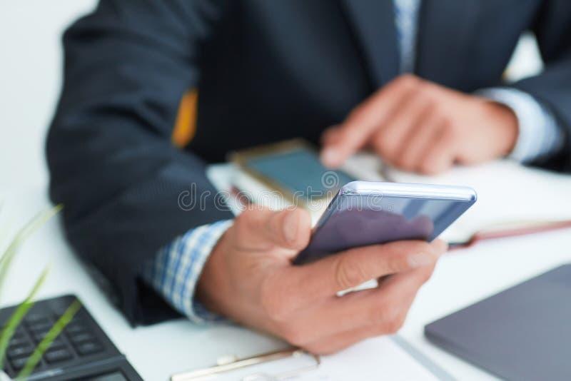 Tir de vue supérieure des mains du ` un s d'homme dans le costume utilisant le téléphone intelligent dans l'intérieur de bureau,  photos libres de droits