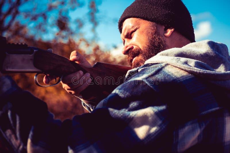 Tir? del disparador de la escopeta Cazador furtivo en Forest Hunter con el arma de la escopeta en caza Gran juego imagenes de archivo