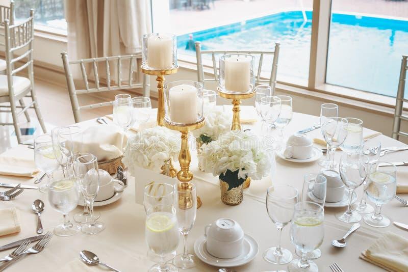 Tir des bougies blanches de pilier dans des candélabres et des bouquets de fleur blanche sur une table l'épousant photo libre de droits