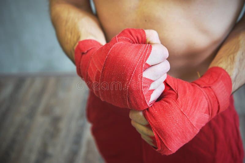 Tir des mains enveloppées avec la bande rouge de boxe du jeune combat de boxeur images stock