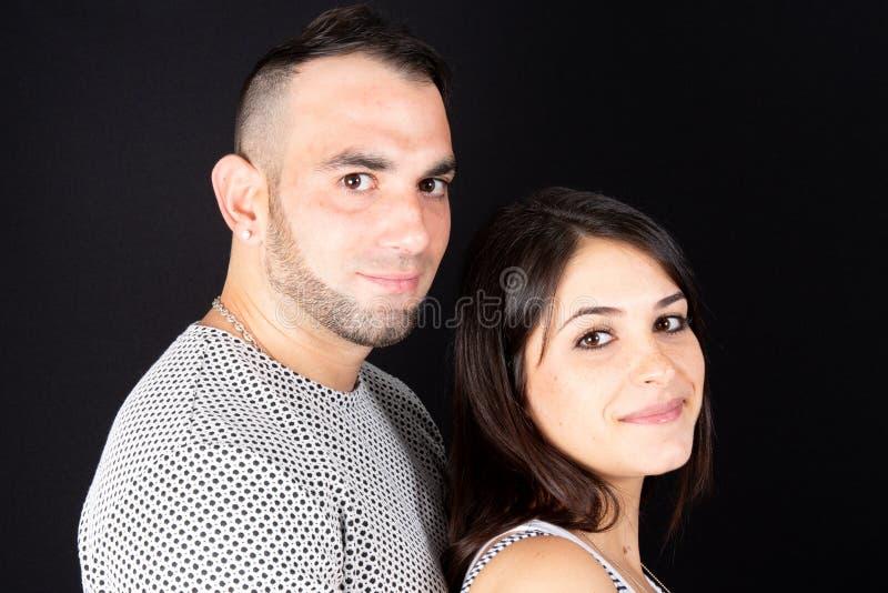 Tir du beau jeune Caucasien de couples se tenant ensemble près du fond noir photo stock