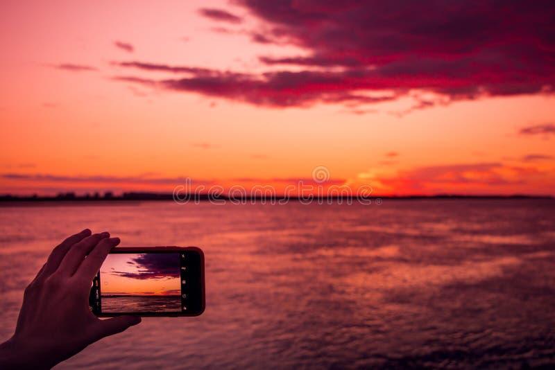 Tir du coucher du soleil sur un smartphone image stock