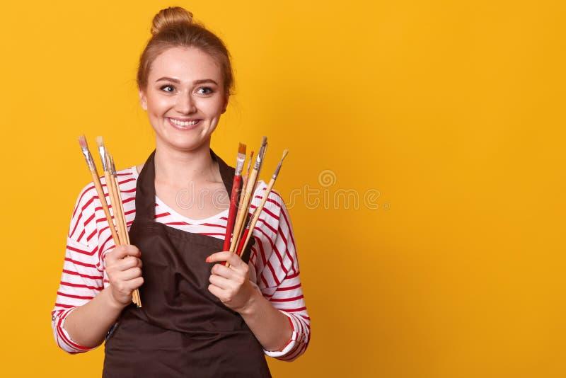 Tir? du jeune peintre caucasien travaillant dans son studio Peinture cr?ative de jeune femme sur la toile dans son atelier photos libres de droits