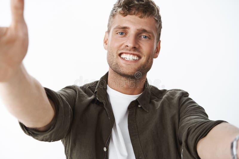 Tir en gros plan d'ami bel tendre affectueux et s'inquiétant avec le sourire d'oeil bleu et blanc large tirant des bras vers photos libres de droits