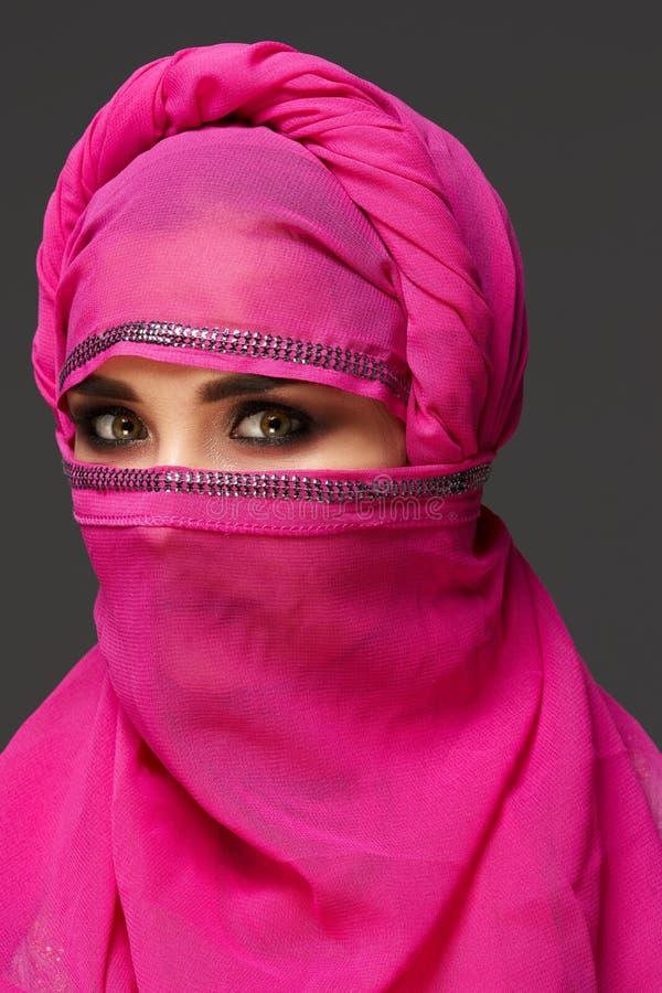 Tir en gros plan d'une jeune femme avec du charme portant le hijab rose d?cor? des paillettes type arabe photographie stock