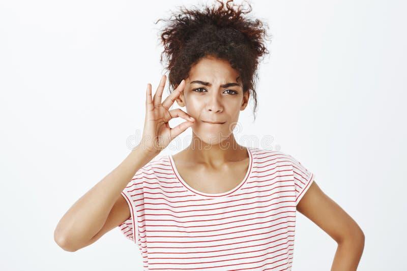 Tir en gros plan de femme à la peau foncée attirante déterminée sérieuse, de lèvres de froncement de sourcils et pinçantes et de  photos libres de droits