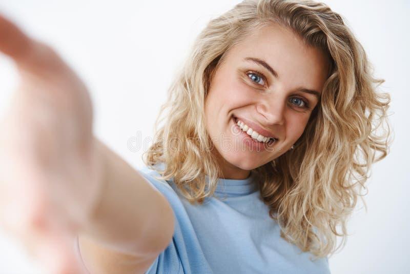 Tir en gros plan de femme attirante heureuse amicale et sociable avec des yeux bleus et le sourire sincère atteignant la caméra a photos stock